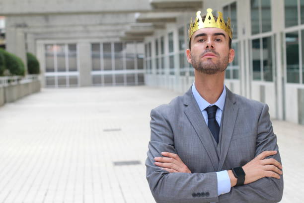 arrogant businessman with crown in office space - arrogance stock pictures, royalty-free photos & images