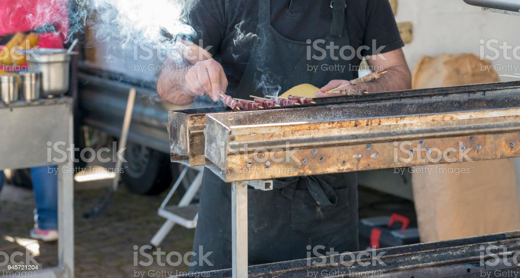 Arrosticini on the grill while turning, Abruzzi skewers of sheep cooked on the grate and on a special brazier - foto stock