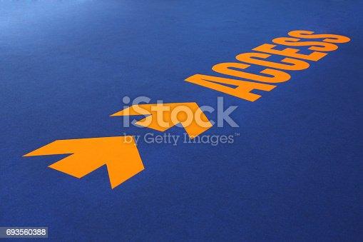 istock Arrow access sign on blue carpet. 693560388