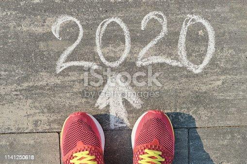 1170070487 istock photo 2020 arrow forward, written on gray sidewalk with woman legs in sneakers, top view 1141250618