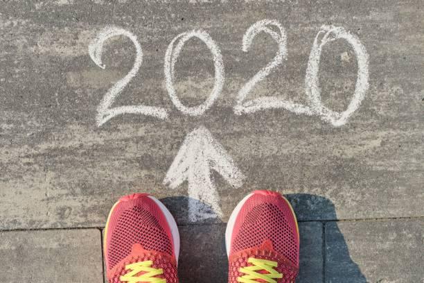 2020 flecha hacia adelante, escrito en la acera gris con las piernas de la mujer en zapatillas, vista superior - foto de stock