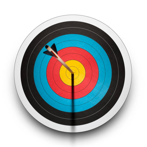 arrow in the bullseye of an archery target - sports target stock photos and pictures