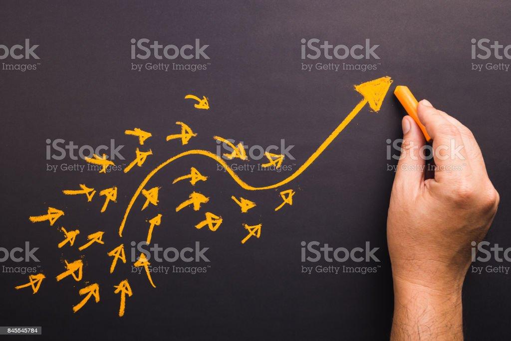 Arrow Leader Hand draw a curve arrow leader with many small follower on chalkboard Adulation Stock Photo