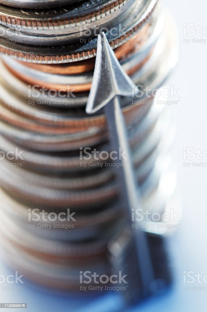 Arrow Leaning Against Stack Of Coins stock photo