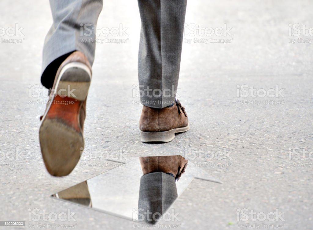 Arrow mirror and mans shoe on street stock photo