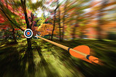 Archery concept of an arrow flying through the air at high speed toward the center of a distant target with motion blur effect. The arrow and target are rendered in 3D.