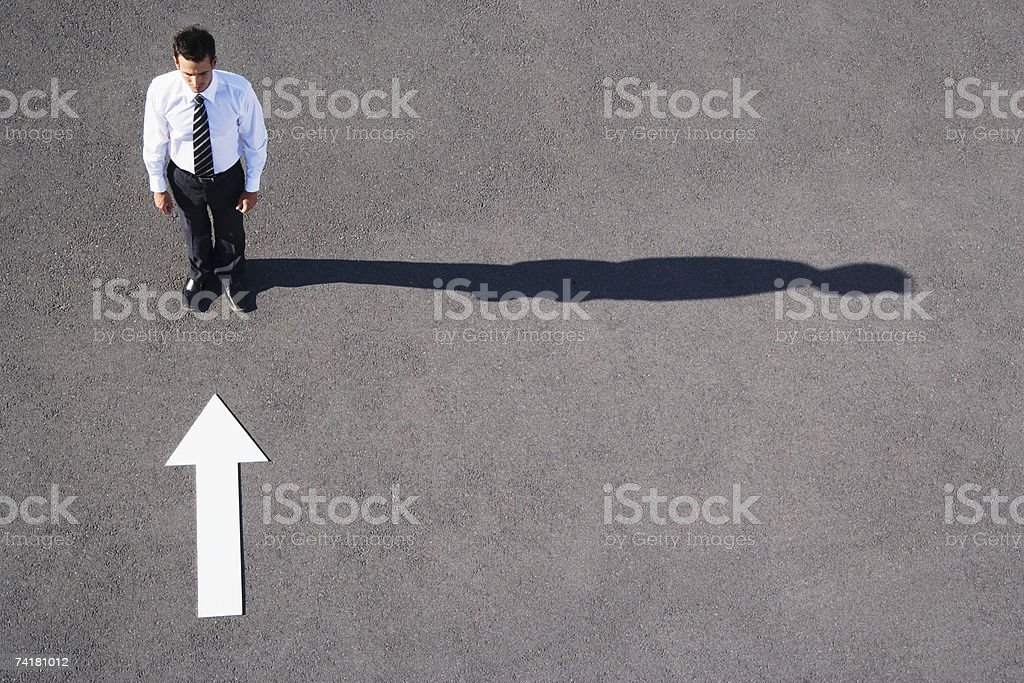 Arrow on pavement pointing toward businessman royalty-free stock photo