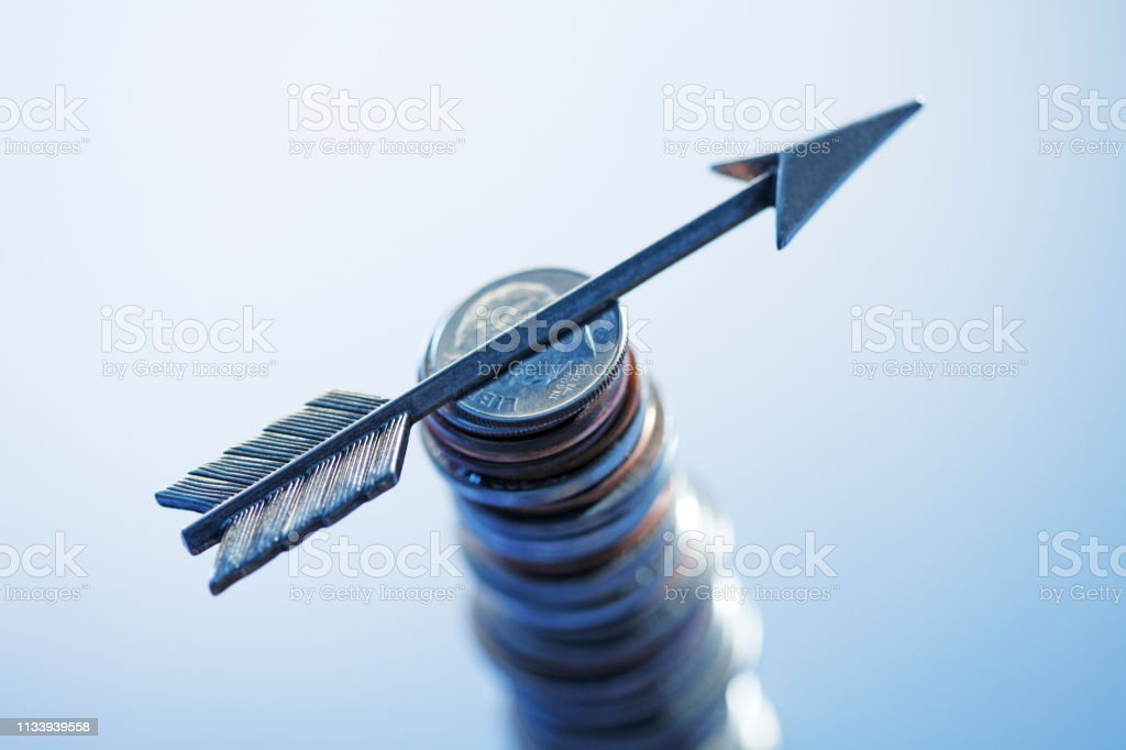 Arrow On Top Of Stack Of Coins stock photo