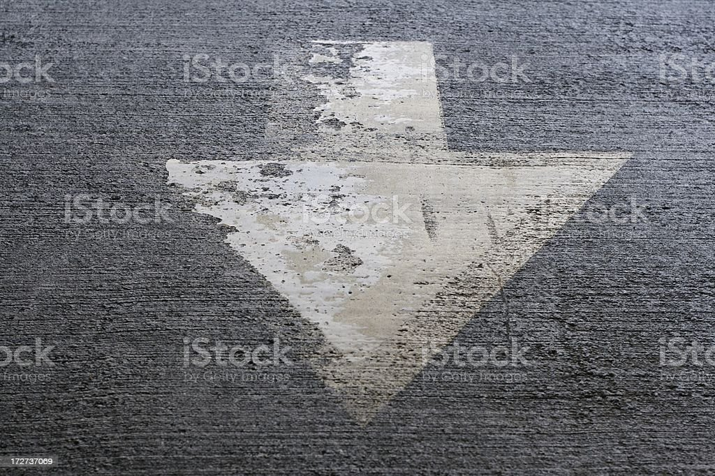 Arrow pointing down on asphalt royalty-free stock photo