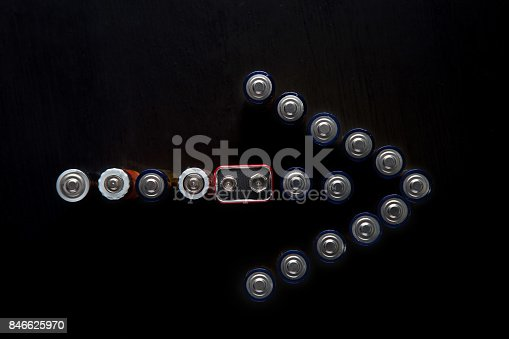 istock Arrow pointing right made of used batteries on black background with copy space 846625970