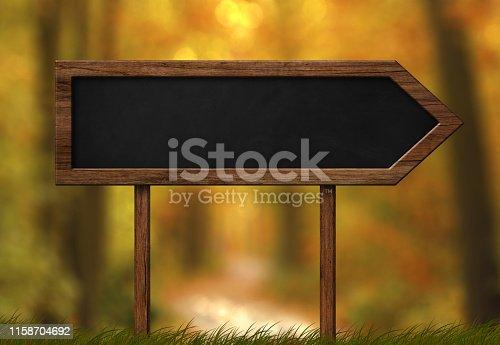 istock Arrow shaped blackboard sign autumn forest background 1158704692