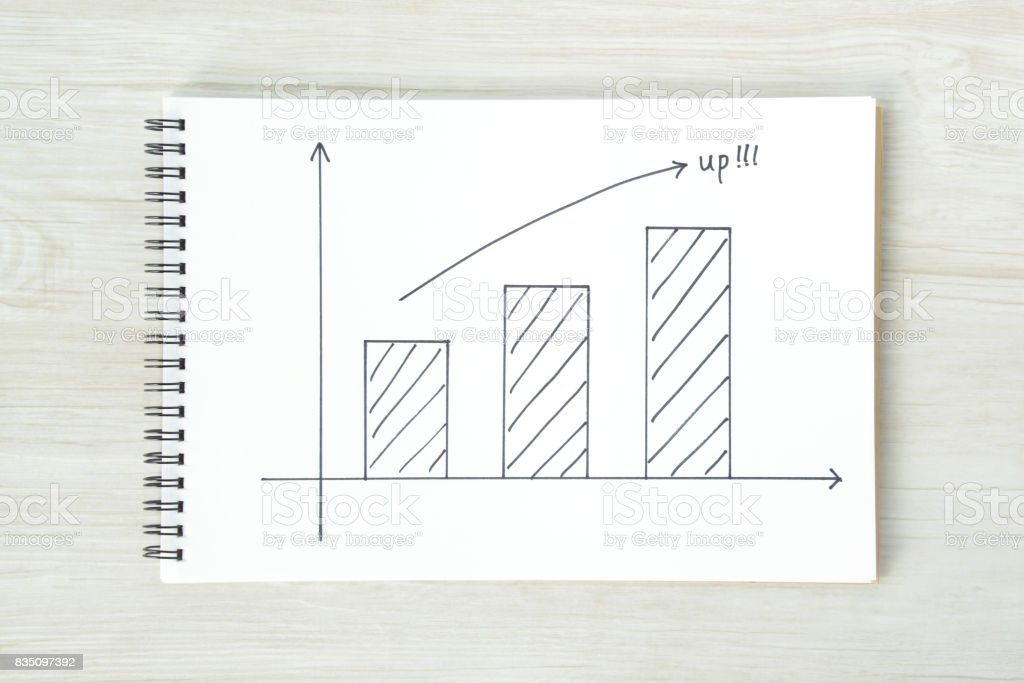 Arrow sign and bar graph on sketchbook stock photo
