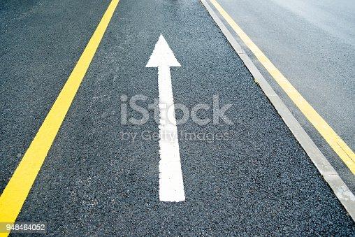 168589045 istock photo Arrow sign on asphalt road 948464052