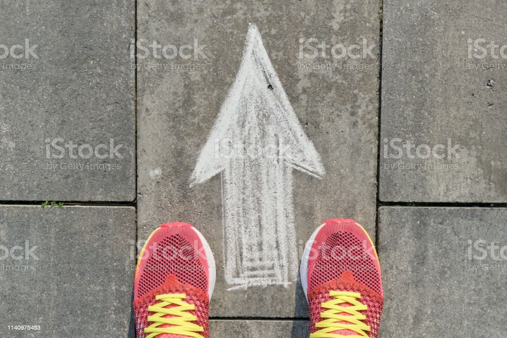 Arrow sign painted on gray sidewalk with women legs in sneakers, top view - Foto stock royalty-free di Abbigliamento casual