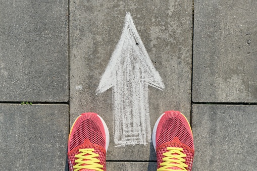 Arrow Sign Painted On Gray Sidewalk With Women Legs In Sneakers Top View - Fotografie stock e altre immagini di Abbigliamento casual