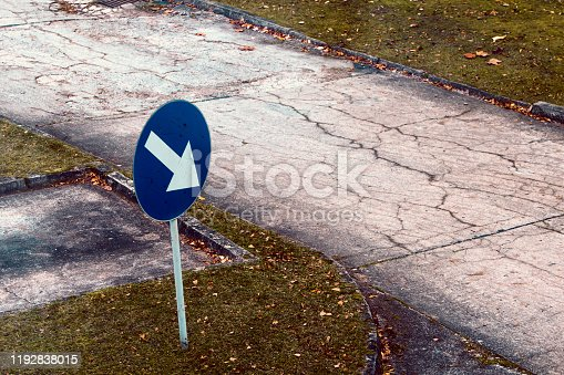 istock Arrow sign to an empty road in bad condition. 1192838015
