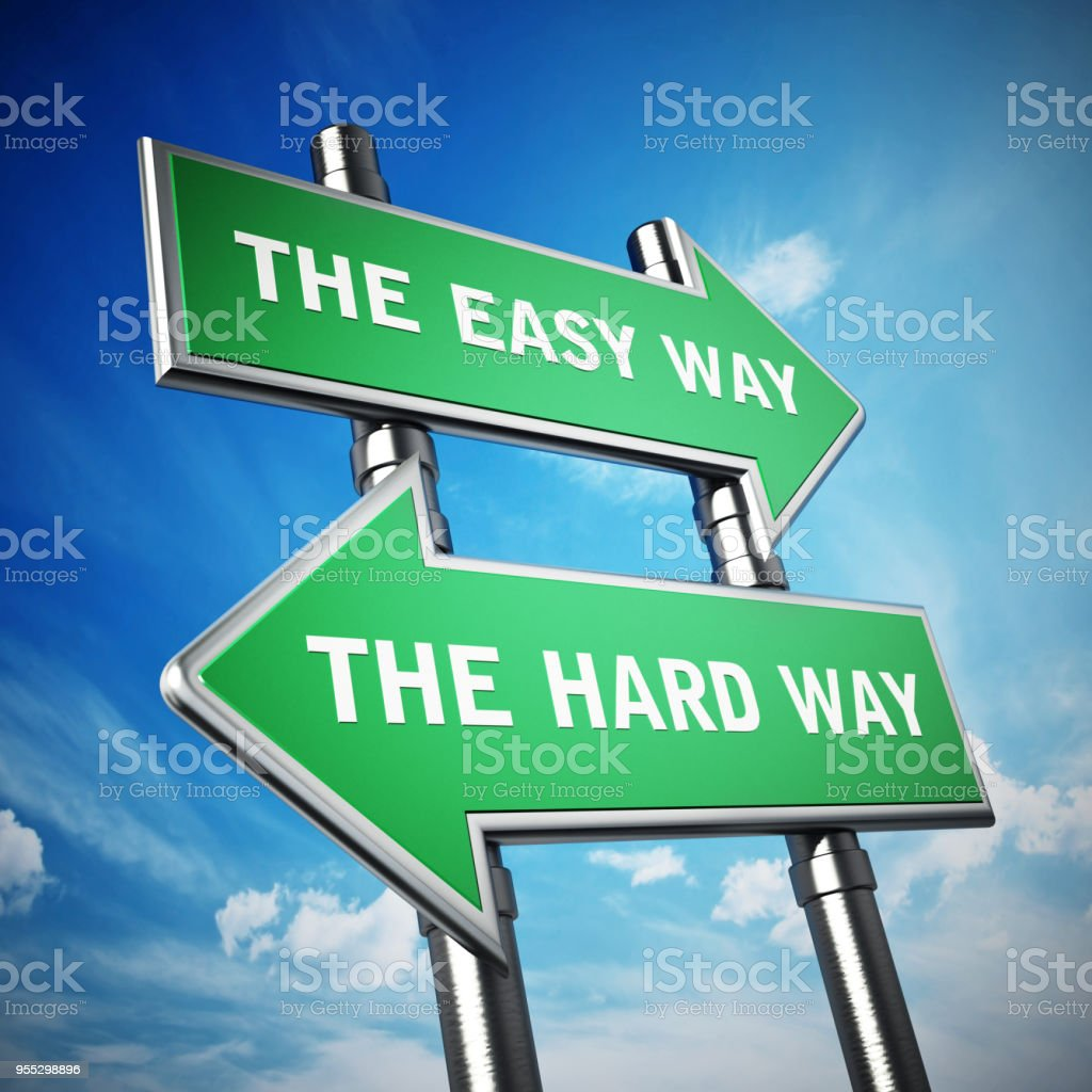 Arrow signboards pointing opposite directions with the easy way and the hard way texts stock photo