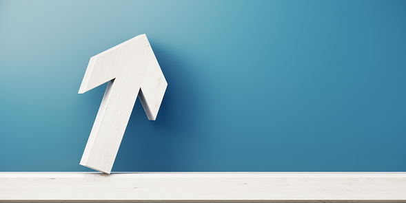 Arrow symbol is standing in front of blue wall. Horizontal composition with copy space, Great use for growth concepts.