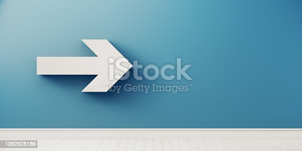 istock Arrow Symbol In Front Of Blue Wall - Growth And Direction Concept 1062628186