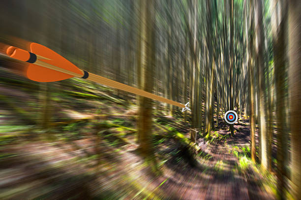 Arrow traveling through air at high speed to archery target - foto de stock