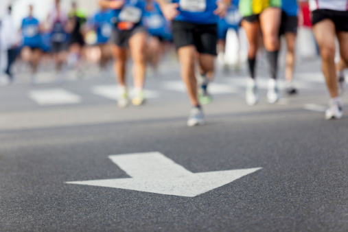 Arrow with line of runners at city marathon
