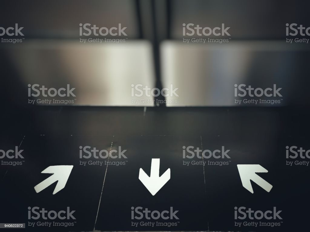 Arrows direction signs (in and out) on floor, in front of subway door; selective focused. stock photo