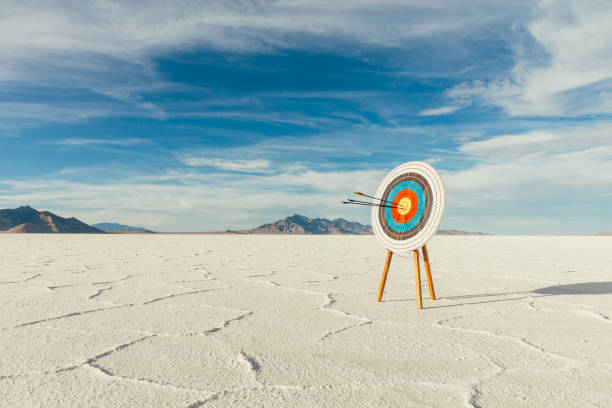 Arrows in Bulls-Eye of the Target Arrows are in the center of the target, hitting their mark in the bulls-eye. Precision is paramount in target shooting. This image symbolizes preparation, determination and accuracy it takes to reach a goal. Image taken on the salt flats of Utah, USA. bonneville salt flats stock pictures, royalty-free photos & images