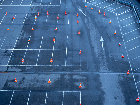Arrows marks and traffic cones on the asphalt on an empty parking lot. high angle view