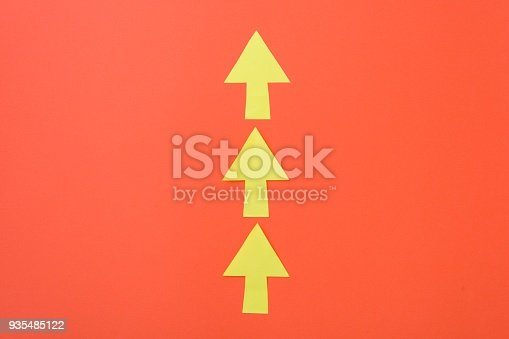 677206912 istock photo Arrows only forward. Three arrows in one direction. Orange background and bright yellow arrows. 935485122