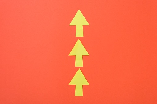 1023882582 istock photo Arrows only forward. Three arrows in one direction. Orange background and bright yellow arrows. 935485122