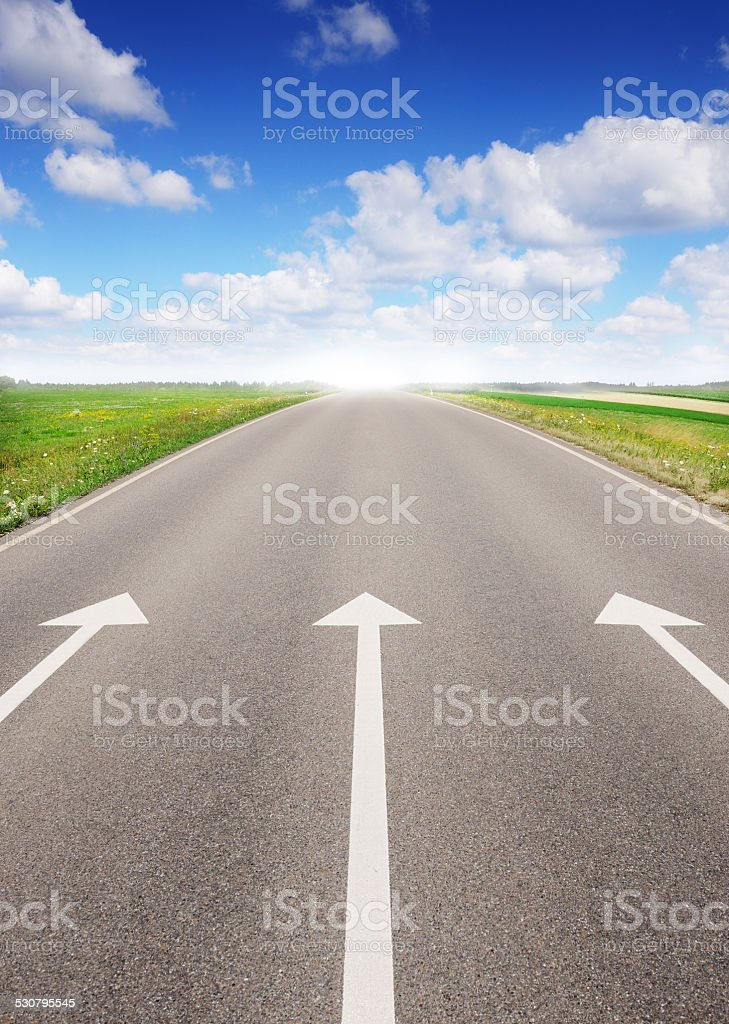 Arrows pointing forward, empty road stock photo
