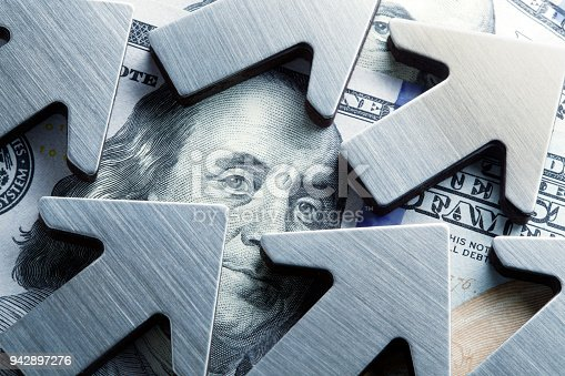 A close up of upwardly pointing arrows surround the face of Benjamin Franklin on the U.S. one hundred dollar bill.