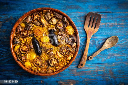 Arroz al horno Oven Rice in clay pot Spain recipe on blue wooden background