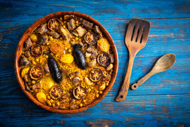 Arroz al horno Oven Rice in clay pot Spain recipe Arroz al horno Oven Rice in clay pot Spain recipe on blue wooden background arroz stock pictures, royalty-free photos & images