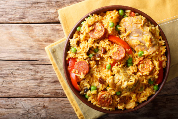Arroz Valenciana with rice, meat, sausage, raisins, vegetables and spices close up in a bowl. horizontal top view Arroz Valenciana with rice, meat, sausage, raisins, vegetables and spices close up in a bowl on the table. horizontal top view from above arroz stock pictures, royalty-free photos & images