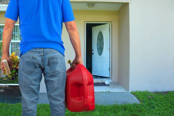 Arsonist man with gasoline can and box of matches preparing to commit arson crime and maliciously burn down a house stock photo