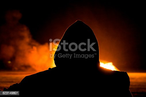 Silhouette of Arsonist in a hooded top looking at a large fire.