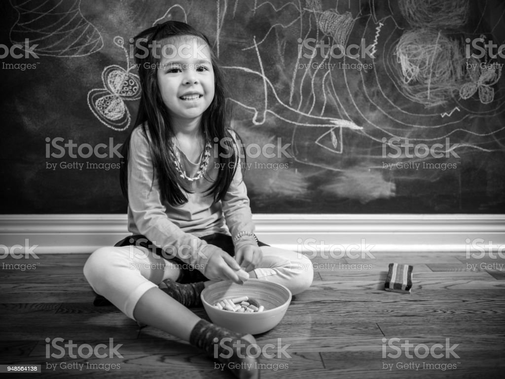 Young mixed race girl sitting on the floor in front of the chalk...