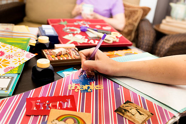Art and Craft: Woman considering arrangment, labels. Scrapbooking. stock photo