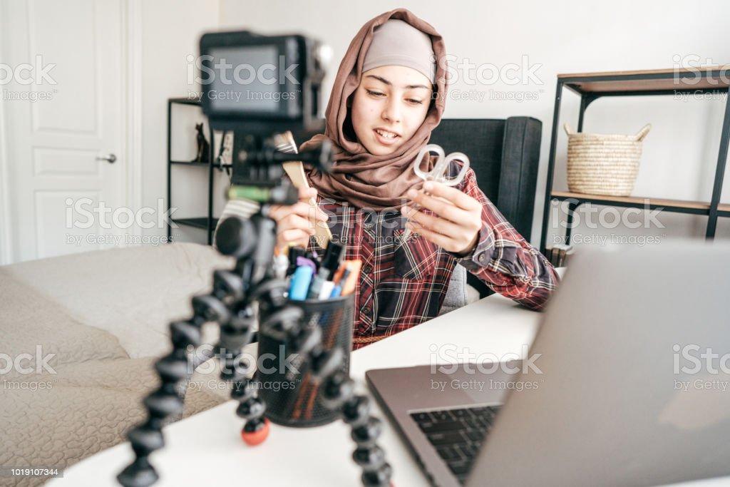 Muslim girl holding scissors and paintbrush.