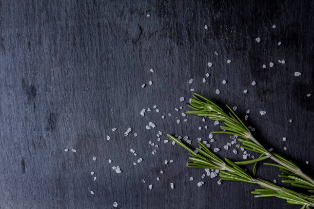 Art background. Food composition with rosemary and coarse salt on a black slate. stock photo