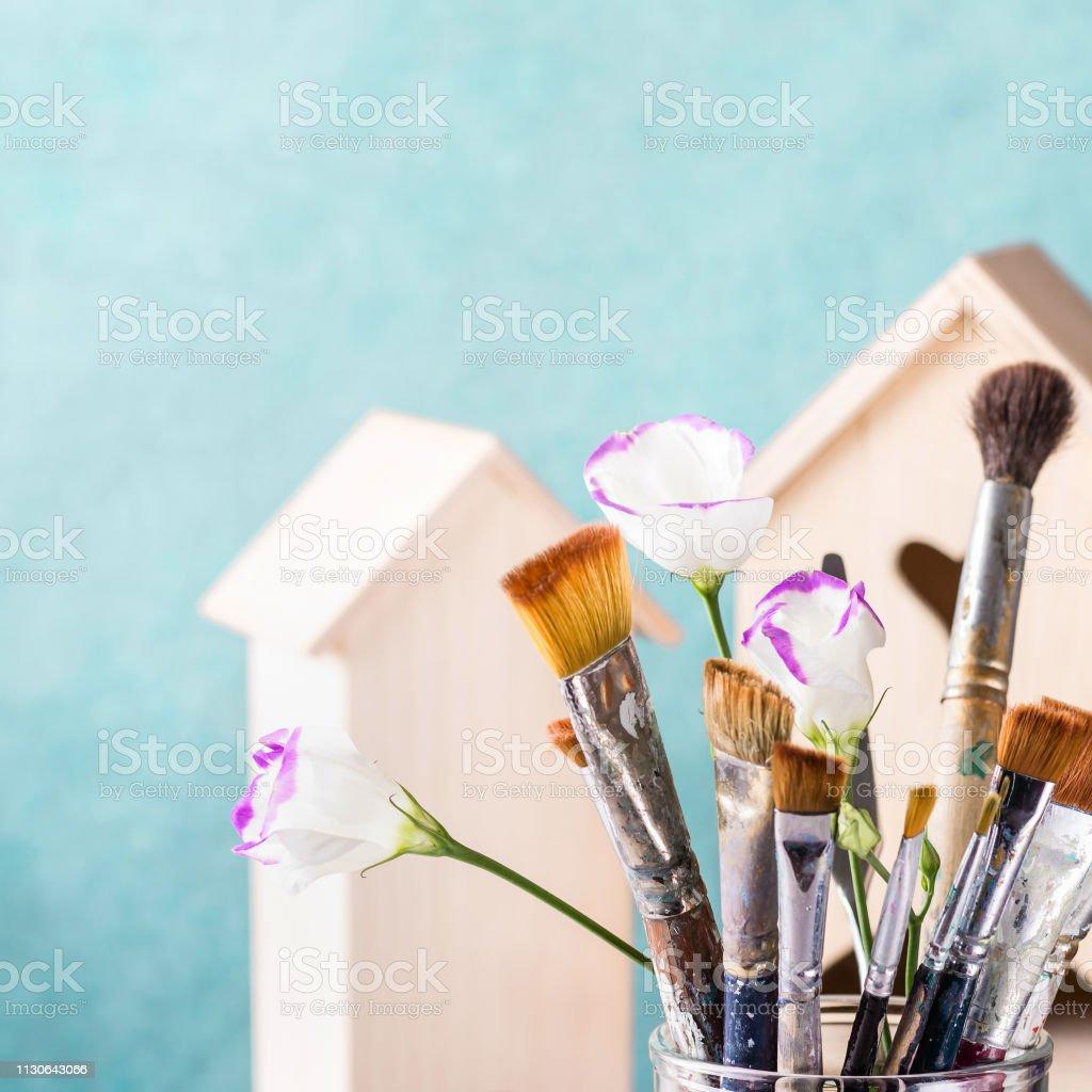Set de cepillo de arte y casa de madera para la decoración en fondo turquesa - foto de stock