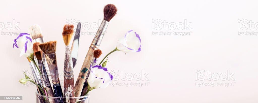 Pinceles de arte y flores en vidrio sobre fondo blanco. Formato de banner - foto de stock