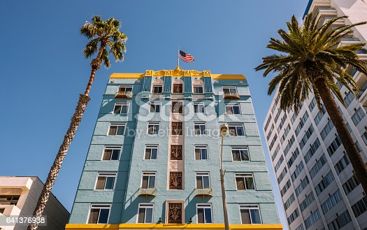 Exterior of Art Decco building in Santa Monica, California. American National flag on top of the building. Palm trees on each side.