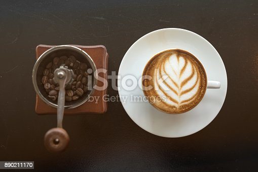 istock Art coffee late with coffee bean inside hand mill; view from top; flat lay photo 890211170
