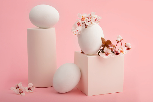 Art composition, white egg with sakura flowers on a pink background. White geometric shapes, cube figure with flowers and an egg. Spring minimalist composition. Easter holiday.