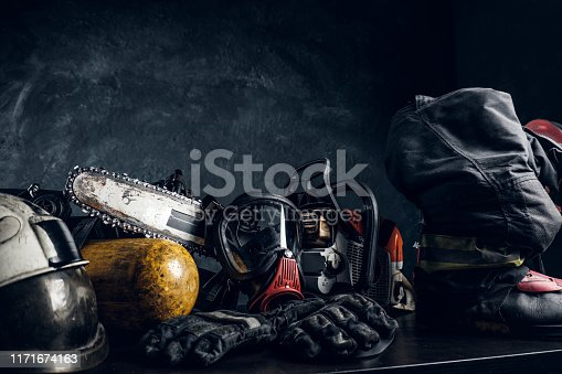 Art composition with safety equipment and respirator, oxygen cylinder and chainsaw on the table. Dark background.