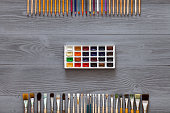 Art creative table background with watercolor paints palette paintbrushes pencils supplies tools on grey wooden desk, artist gray design blank workspace top view from above, flat lay, copy space