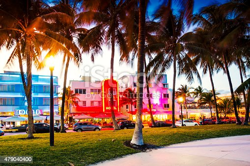 Photo taken at night, on Miami Beach, with famous art deco hotels on background and palm trees.