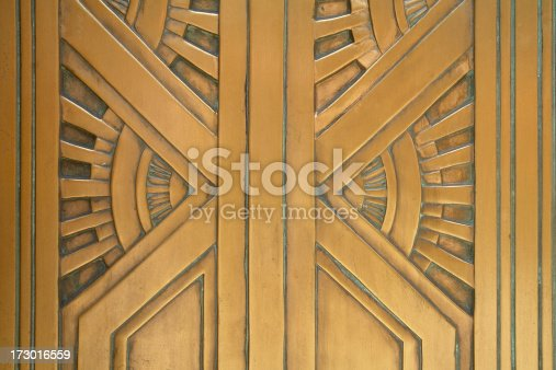Close-up architectural detail from an art deco style bronze door.  The photo was taken in New York City and the composition focuses on the strong vertical elements juxaposed with radiating diagonals suggesting the rays from the sun. The detail is rich with golden tone hues and patination conducive to a building from 1929.